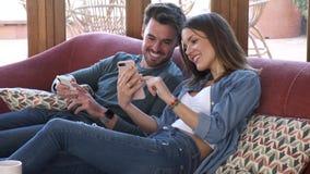 Mooi jong paar die zij mobiele telefoon terwijl thuis het zitten op bank gebruiken stock videobeelden