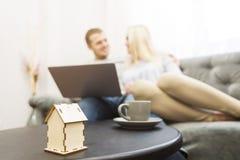 Mooi jong paar, gebruikend laptop en kiezend een nieuwe flat Lay-out van het huis in de voorgrond stock afbeeldingen