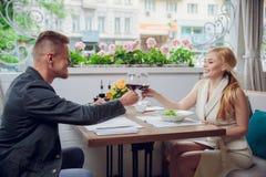 Mooi jong paar met glazen rode wijn in luxerestaurant Stock Afbeelding