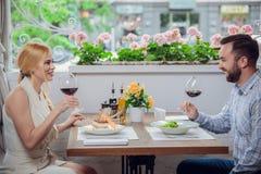 Mooi jong paar met glazen rode wijn in luxerestaurant Stock Fotografie