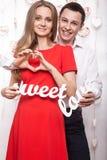 Mooi jong paar met woorden Zoete liefde die de vorm van harthanden tonen De dag van de valentijnskaart Stock Afbeelding