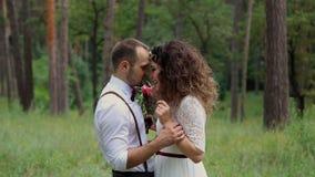 Mooi jong paar op Boheemse stijlmanier in het bos die elkaars ogen onderzoeken stock videobeelden