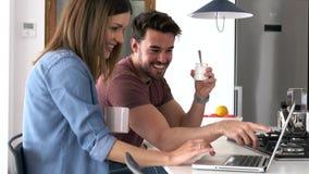Mooi mooi jong paar thuis gebruikend hun laptop en hebbend ontbijt in de keuken stock footage