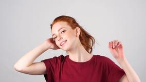 Mooi jong roodharigemeisje die en camera op witte achtergrond dansen bekijken Langzame Motie stock video