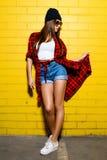 Mooi jong meisje die en dichtbij gele muurachtergrond stellen glimlachen in zonnebril, rood plaidoverhemd, borrels Royalty-vrije Stock Foto's