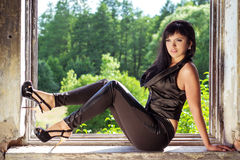 Mooi jong sexy meisje in een zwart kostuum met zwart lang haar met mooie make-upzitting in het venster van oude verlaten bu Stock Foto