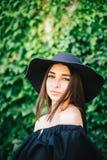Mooi jong sexy meisje met donkere huid en brunette met zwart haar gekleed in een modieuze zwarte kleding en een hoed op achtergro stock afbeeldingen