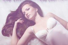Mooi jong sexy meisjesbrunette met make-up in witte bodysuit in de Studio op een zwarte achtergrond Royalty-vrije Stock Foto