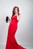 Mooi jong sexy slank roodharig meisje die hoge hielen van een de stiekeme zijde rode kleding, in alcoholische intoxicatie dragen stock foto