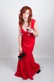 Mooi jong sexy slank roodharig meisje die hoge hielen van een de stiekeme zijde rode kleding, in alcoholische intoxicatie dragen stock foto's