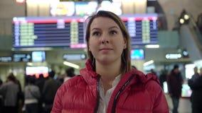 Mooi jong toeristenmeisje in internationaal luchthaven of station, dichtbij de raad van de vluchtinformatie stock videobeelden