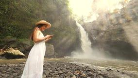 Mooi Jong Toeristenmeisje in Lange Witte Kleding en Straw Hat Making Photos van Verbazende Tegenungan-Waterval die Mobiel Smart g stock footage