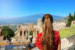 Mooi jong vrouwelijk model in de ruïnes van het oude Griekse theater in Taormina met de vulkaan van Etna op de achtergrond, Sicil stock fotografie