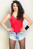 Mooi jong vrouwen krullend haar, jeansborrels en rood mouwloos onderhemd Royalty-vrije Stock Afbeelding