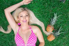 Mooi jong vrouwenblonde in een roze bikini die op het gras met twee ananassen liggen stock foto