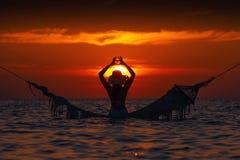 Mooi jong vrouwensilhouet met schommeling het stellen in het overzees op zonsondergang, maldivian romantisch landschap royalty-vrije stock afbeeldingen