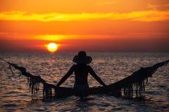 Mooi jong vrouwensilhouet met schommeling het stellen in het overzees op zonsondergang, maldivian romantisch landschap royalty-vrije stock fotografie