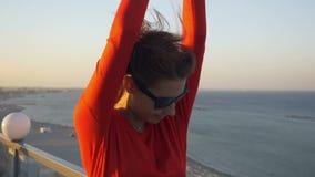 Mooi jong wijfje die op het dak met een strandmening dansen stock footage