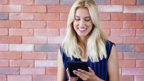 Mooi jong wijfje in elegante uitrusting die moderne tablet gebruiken stock videobeelden