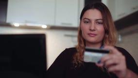 Mooi jong wijfje met lang haar online bankwezen die een mobiele computer en een creditcard gebruiken die een goede stemming hebbe stock video
