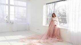 Mooi jong zwanger meisje in roze lange kleding stock footage