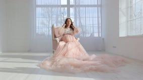 Mooi jong zwanger meisje in roze lange kleding stock videobeelden
