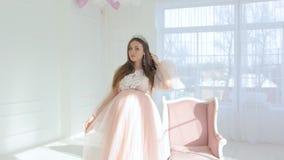 Mooi jong zwanger meisje in roze lange kleding stock video