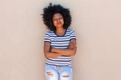 Mooi jong zwarte die zich met die wapens bevinden door muur worden gekruist Stock Fotografie
