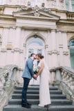 Mooi jonggehuwdepaar in de kus van het liefdeaandeel op oude treden bij het oude Oostenrijkse paleis royalty-vrije stock fotografie