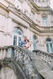 Mooi jonggehuwdepaar die op oude treden bij het oude Oostenrijkse paleis omhelzen stock afbeelding