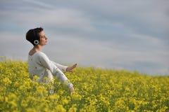 Mooi Kaukasisch meisje die aan muziek met hoofdtelefoon in Th luisteren Stock Afbeeldingen
