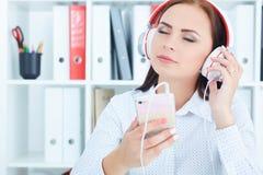 Mooi Kaukasisch meisje die in hoofdtelefoons aan muziek van smartphone in bureau luisteren royalty-vrije stock afbeeldingen