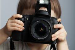 Mooi kind binnen met professionele camera Weinig jongen met lang blond haar die in de Studio fotograferen Royalty-vrije Stock Afbeelding