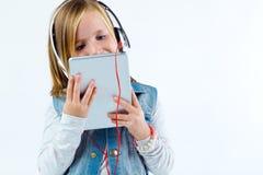 Mooi kind die aan muziek met digitale tablet luisteren Stock Foto