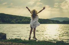 Mooi kind die bij het water springen stock fotografie