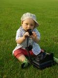 Mooi kind met telefoon op het groene gras stock afbeelding