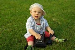 Mooi kind met telefoon op het groene gras royalty-vrije stock fotografie
