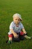 Mooi kind met telefoon op het groene gras stock foto