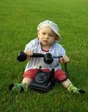 Mooi kind met telefoon op het groene gras stock fotografie