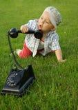 Mooi kind met telefoon op het groene gras stock foto's
