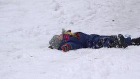 Mooi kind op slee, jong geitje die neer en op de sneeuw, de wintersport, ongeval rollen vallen stock footage