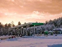 Mooi klein benzinestation voor het bijtanken van auto's met brandstof, benzine en diesel bij zonsondergang in de winter stock foto's