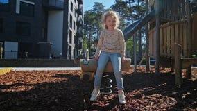 Mooi klein meisjesspel in speelplaats bij de lente stock footage