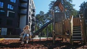 Mooi klein meisjesspel in speelplaats bij de lente stock video