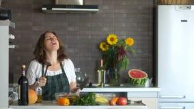 Mooi krullend brunette in een fartuh die in de keuken met een mes en een ingelaste lepel dansen Modern keukenbinnenland stock footage