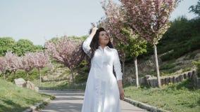 Mooi krullend brunette in witte kleding die in bloeiend park lopen stock video