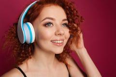 Mooi krullend-haired jong roodharig meisje met hoofdtelefoons De gelukkige jonge zakken van de meisjesholding op een witte achter royalty-vrije stock foto