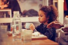 Mooi krullend meisje die blauwe sweater het drinken thee in cafetaria dragen stock afbeeldingen