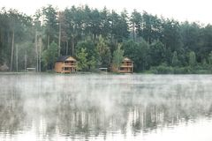 Mooi landschap met bos en huizen dichtbij meer Het kamperen seizoen Stock Fotografie