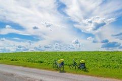 Mooi landschap met een groen gebied en een mooie hemel met wolken, twee fietsen aan de kant van de weg op een halt stock foto